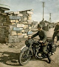 German soldier in motorcycle reading mixed road signs