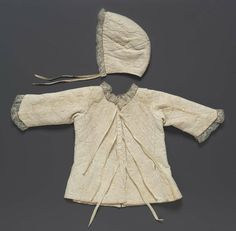 Infant's jacket and cap, probably Germany, 18th century. White linen with design of tangent concentric circles crossed by a lattice. Pulled in quilting worked in back-stitch, with small figures worked in white linen in spaces between circles. Narrow bobbin lace around neck and sleeves.