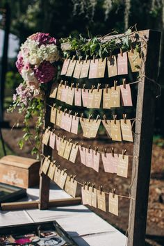 Escort cards hung from clothespins.   Invitations: MLC Designs LLC  Floral Designer: Justin Wham of JW Weddings and Events