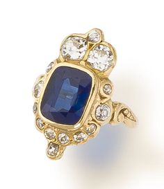 A sapphire and diamond ring  centering a cushion-shaped sapphire within a surround of old mine and old European-cut diamonds, completed by scrolling gold shoulders and a plain mount