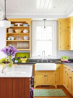 Schoolhouse Electric-type drop lights. Cabinets go up to short sofit. Feet on kitchen sink cabinet. Plate rack. dark counters. Wood floor. Gray walls. Paneled ceiling. Bright cabinets.