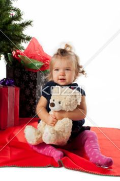 cute toddler sitting with her teddy bear by a christmas tree. - Cute toddler sitting with her teddy bear with Christmas presents and Christmas tree in the background. Model: Hannah Phillips