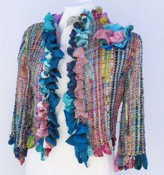 Chaqueta corta en abundancia de estampados hindúes en tonos jeans, rebordeada con bullones en géneros acordes. Acompaña sutil broche-flor en tonos rosa y turquesa.  Medidas: talla 44. Técnica: telar manual. Hilados: algodón y seda. Géneros: seda y gasa de pañuelos hindúes.