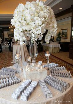 A larger-than-life tumble of white orchids made for a seriously stylish arrangement on a placecard table at @Mandy Dewey Seasons Hotel Westlake Village.