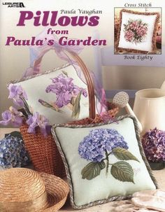"""Pillows from Paula's Garden: Book 80"" a cross stitch leaflet by Paula Vaughan. The book includes nine projects: Black-eyed Susan, Hydrangeas, Dusty Pink Roses, Magnolia, Light Pink Wild Roses, Zinnias, Dark Pink Wild Roses, Iris, Dark & Light Pink Wild Roses. ***Pictured are Iris and Hydrangeas,***"