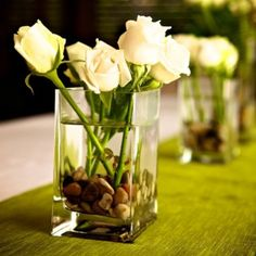 Simple traditional white rose centerpiece on a gorgeous green table runner