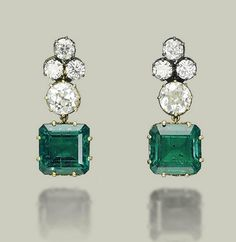 AN IMPORTANT PAIR OF EMERALD AND DIAMOND EARRINGS  Set with two octagonal-cut emeralds, weighing approximately 10.01 and 9.36 carats, to the old European-cut diamond surmount and trefoil top, mounted in gold collets with heart-shaped galleries