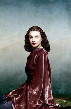 Vivien Leigh in a maroon colored full-sleeved dress sitting down facing camera