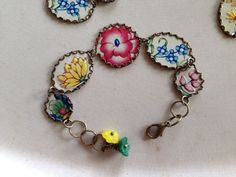 Gorgeous bracelet bursting with colorful flowers...perfect for summer. It was crafted from a vintage tea tin by carefully hand cutting and placing