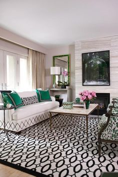 This is a living room, but great inspiration for a bedroom. I love the green, black and white together, especially the pillows. Plus the pink flowers really make the room pop!