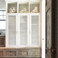 Chic beach cottage mudroom boasts built-in shelves filled with white sea coral stacked upon white louvered lockers adorned with brass pulls.
