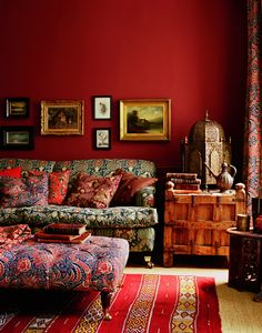 The ethnic furniture and mixed fabric patterns are great but the red walls are the real focal point in this cozy eclectic living room.