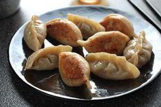 """-Meat and Chinese Chive Pot Stickers (Guōtiē) Recipe-Pot stickers supposedly started out as boiled dumplings that a chef forgot about in the wok (""""guō"""") and they stuck (""""tiē"""") after the water had cooked away. His guests loved the contrast between succulent filling, tender-chewy skin, and crusty bottom, and thus the pot sticker was born. The modern way to mimic the chef's delicious accident is to cook pot stickers in a skillet with water and oil, which steams the dumplings and fries their bot..."""