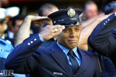 """On 9/11, the New York City Police Department lost 23 officers. The Port Authority police lost 37. The FDNY's dead numbered 343. Here, firefighter Tony James cries while attending the funeral service for New York Fire Department chaplain Mychal Judge at New York's St. Francis of Assisi Church, September 15, 2001. Photographer Joe Raedle, who attended and photographed funerals for weeks after September 11, told LIFE.com of this shot: """"Anytime you see a fireman or a symbol of strength breaking d..."""