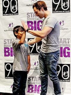 Sebastian Stan high fiving a kid dressed similarly to him