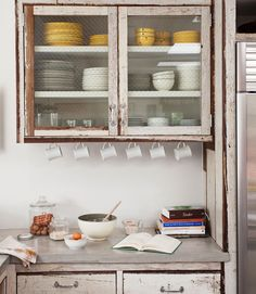To the left of the fridge, upper cabinets sport glass doors lined with chicken wire.   - CountryLiving.com