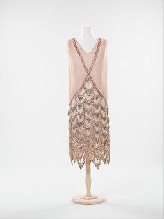 Rhinestone-embellished pink silk evening dress, French, 1925. This dress takes on the tubular shape which was the dominant silhouette of the 1920s. The sheer top, adorned with rhinestones, intersects at the waist to create a skirt consisting of tiers of scalloped beadwork of a typical Art Deco pattern. The execution of the design of the skirt is exquisite and highly impressive.