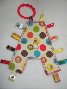 Alphabet Monogram Taggie in your letter choice.    Measures about 8 x 8 inches.    Quality cotton fabrics with coordinating ribbons for your baby.