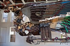 An installation featuring two monumental Phoenixes made from found materials