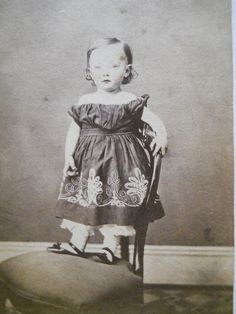 Qute girl standing on a chair.