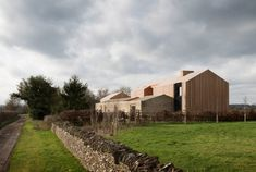 Bureau de Change has covered Long House, which is formed of a pair of interlocking barn-style volumes, in stone and larch that has been charred for effect. Chicken Shed, Stone Siding, Long House, Internal Courtyard, Dry Stone, Brick Facade, Ventilation System, Change, Modern Exterior