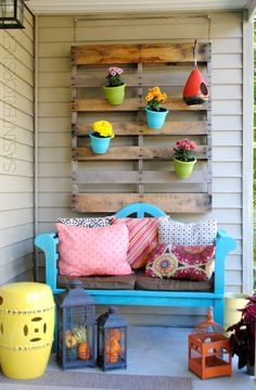 Pallet on wall behind porch swing to decorate differently throughout the year