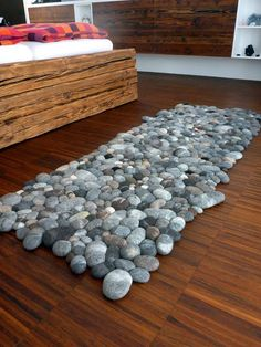 If you want to add a bit of nature to your home decor this pebble carpet would be a fine option.    Pebbles of different sizes form this soft, stimulating carpet. The elegant rug has an exciting relief effect. The handmade pebbles are really unique and modeled in the form of diversity and variation in nature. Each felted stone is different to the others. The wool is felted by hand. A foam core is surrounded by 100 % wool.   The carpet looks good, and makes you feel like you are in the middle…