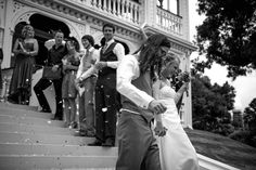 Bride and groom descend the steps at their wedding at Alberton House, Mt Albert, Auckland. Black and white. Confetti rose petals are being thrown. BeSo Studios create beguiling fine art family photographs for the walls of the most discerning clients homes. We specialise in wedding and family portrait photography, and supply prints on the highest quality media, framed in beautiful conservation standard frames. We are a high end studio located in the beautiful city of Auckland, New Zealand.