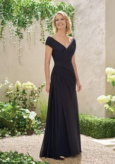 Stretch Illusion with Stretch lining dress with a portrait neckline and gathering at the bodice and throughout the skirt - all in the color black.