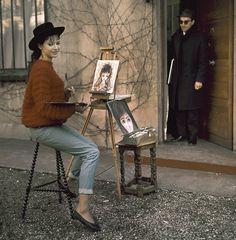 1964. L'actrice Anna Karina pose entrain de peindre dans son jardin sous l'œil amusé de son mari le réalisateur Jean-Luc Godard . Mais l'année 1964 sera aussi celui de leur divorce. ils s'étaient mariés en 1961. Elle aura joué dans 7 de ses films , dont quatre après leur séparation. photo : Jack Garofalo/Paris-Match.