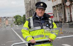 A member fo the Irish Garda blocks the route to the Dublin Memorial Gardens in advance of the Queen and Duke of Edinburgh's visit on May 2011 in Dublin, Ireland. Dublin is preparing for the Queen. Erin Go Bragh, Edinburgh, Memorial Gardens, Irish, Rain Jacket, Windbreaker, Memories, Dublin Ireland, Duke