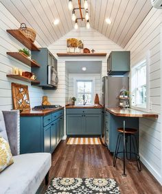 Gorgeous green custom cabinets and eight feet of butcher block countertops provide a warm contrast to the white shiplap walls.