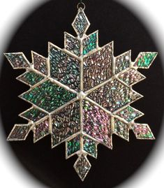 This stained glass snowflake was handcrafted in my home based studio using transparent, iridized glass with different textures. Measuring