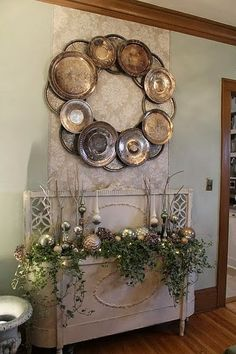 Wall Art Wreath with silver plates and platters.  Like that they used a single sheet of wallpaper behind it to show it off.