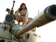 "Kurdish pop star Helly Luv tells reviewers of her new single, ""Revolution,"" that she refused to imitate or fabricate any of the suffering in the war against the Islamic State in Syria. Wanting to depict the realities of the battlefield for the Peshmerga and ISIS refugees, the golden-high-heel-clad artist filmed her music video less than two miles from the front lines with ISIS."