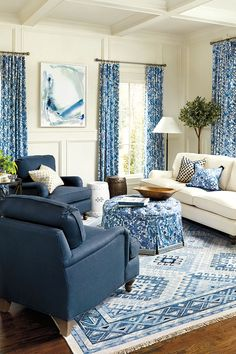 Blue living Room with pattern carpet, ottoman, pillows, draperies
