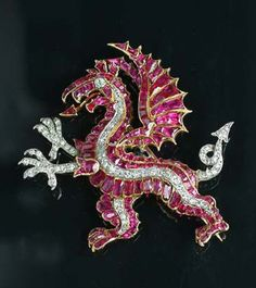 A ruby and diamond dragon brooch, circa 1925,  the stylised dragon set with calibré-cut rubies with single and old brilliant-cut diamond tail, claws and eye detail, and an enamel tongue, length 4.3cm