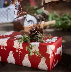A Christmas present wrapped in red paper with Santa Claus pattern and decorated with ribbon and a pine cone.