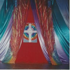 The Rainbow Surrounds The Throne Banner, made in 1994 for International Christian Dance Fellowship Conference in York, England.  It is constructed in satin and lame with the resting Lamb in the centre of the Celtic style cross holding a flag, depicting Jesus' victory over death.  It is surrounded a seven coloured rainbow...