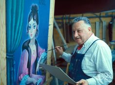 Disney Legend and Imagineer X Atencio with concept art for The Haunted Mansion.