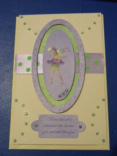 a handmade fairy greetings card. cream purple and green. finished with layers, sentiment, ribbon and crystals.