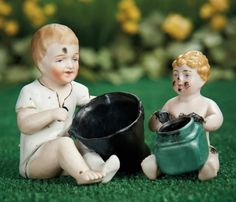 """Two German Bisque Amusing Figurines~~~4"""" (10 cm.) larger. Each is an all-bisque seated child with sculpted hair and painted features, one holding a coal bucket, one holding an inkwell, and each with smudged coal or ink on its face. Generally excellent. Germany, circa 1900."""