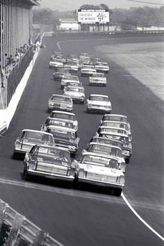 (Courtesy of the Ford Racing Archives) Darlington, SC, May 8, 1965. Junior Johnson (right in photo, on pole) and Marvin Panch (left of photo, 2nd place starter) lean on each other at the start of the Rebel 300 at Darlington Raceway. Johnson would dominate the race and go on to win, while Panch crashed out. Ned Jarrett would win the famed Southern 500 later that year in his '65 Ford. [Note Falstaff Beer sign in turn four; Falstaff was the sponsor of the season's champion prize money before…