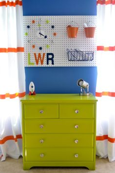 Fun usage of a pegboard to hold baby supplies and display funky nursery accents!