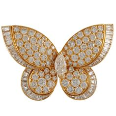 """An 18K gold butterfly, set with round-cut diamonds, trimmed with baguette diamonds, with a marquise shaped diamond at the center. The dimensions are approximately 1' x 1 3/4"". Signed Van Cleef and Arpels. Circa 1980's "" (quote)"
