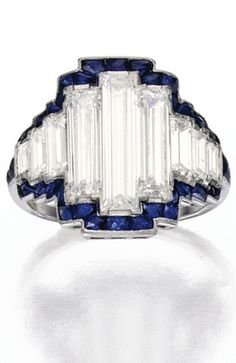 PLATINUM, DIAMOND AND SAPPHIRE RING Set with nine baguette diamonds weighing approximately 2.40 carats, bordered by French-cut sapphires, circa 1925.