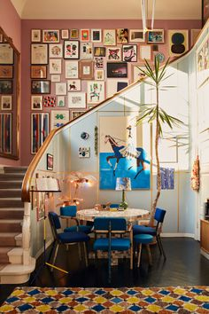 Blue and pink living space with large gallery wall in the staircase in a colorful art-filled home The Nordroom - The Colorful Copenhagen Home of an Art Collector<br> A home in Copenhagen filled with art, color and textures