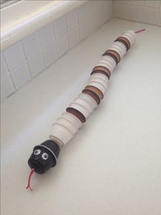 coffee pod snake for school project on recycling - fishing line and beads used for spacing. Googly eyes. Electrical tape tongue.