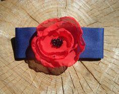Une broche en tissu unique fait la différence entre les personnes distinguées et les autres.   Elle s'accroche par une attache classique de 25mm couleur argent. Elle est entièrement cousu main.  Peut se porter sur une chemise, une robe, un pull, un t-shirt, une écharpe, tout est permis.  Dimensions: 9 cm x 4 cm Tissu satin bleu marine 50% polyester 50% viscose  Tissu rouge voile