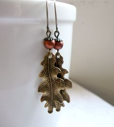 "These sweet oak leaf and acorn earrings bring a little touch of nature to the lobes. They're comprised of solid brass leaf charms, along with copper glass beads, which look like tiny acorns sitting atop the leaves. Adorable in their woodland nature, these earrings come on brass ear wires. The leaf charms measure 5/8"" x 1.5""."